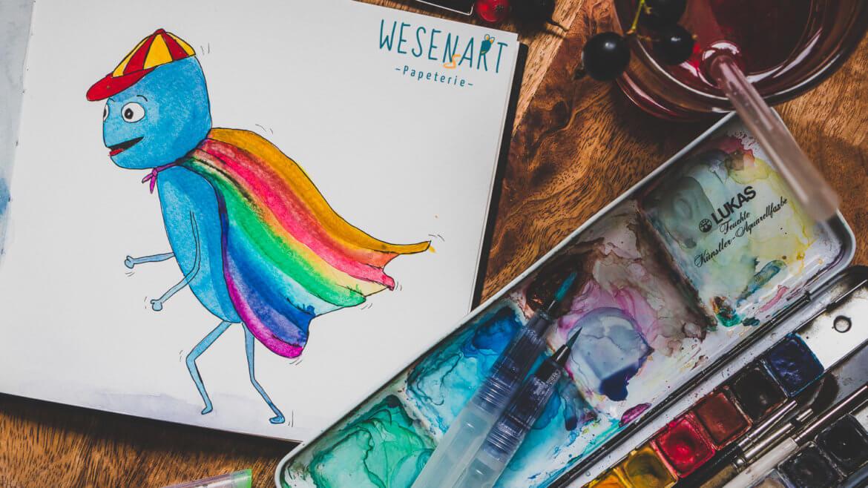 WESENsART – Alex läuft mit einem Regenbogenumhang herum.