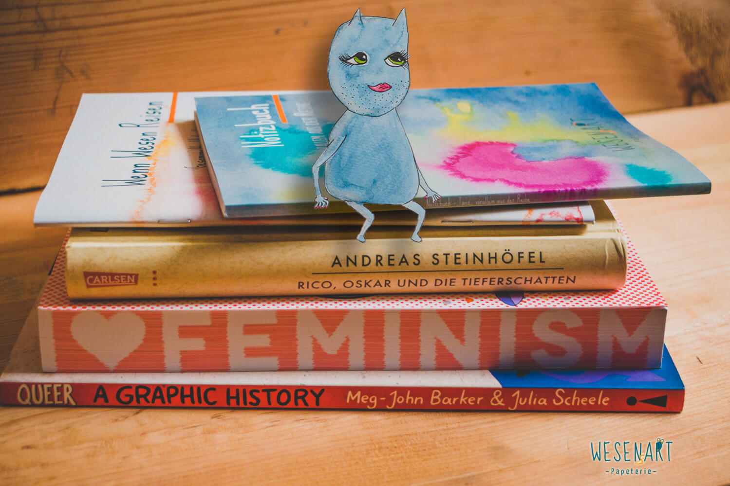 WESENsART – Ally sitzt auf einem Stapel Lieblingsbücher