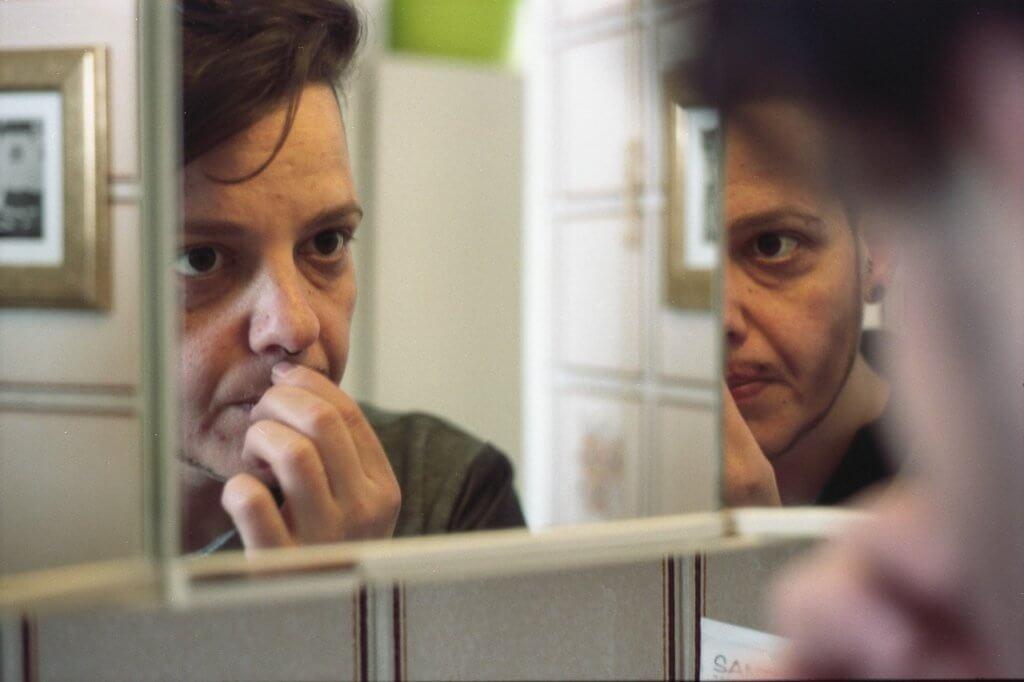 Stephanie Weber schlüpft vor dem Spiegel in ihre Drag King Rolle Hans Schwanz (Foto von Hanna Vogel)