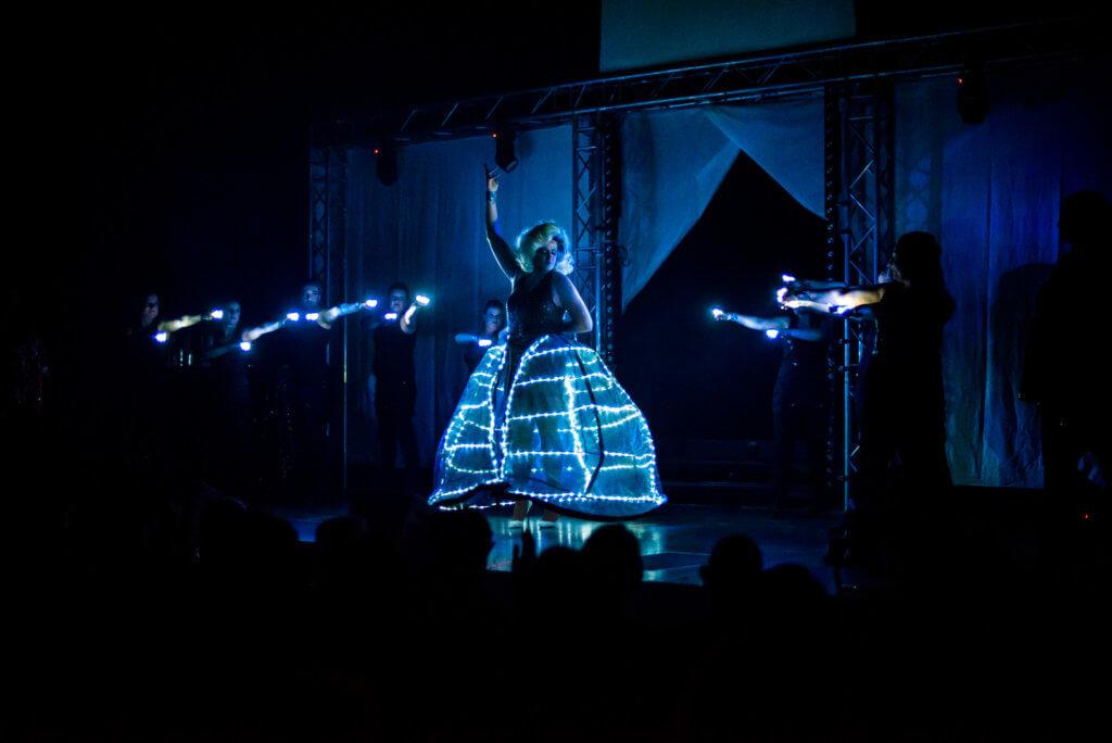 Max Engelmann als Lady Maxime im leuchtendem Kleid auf der Bühne