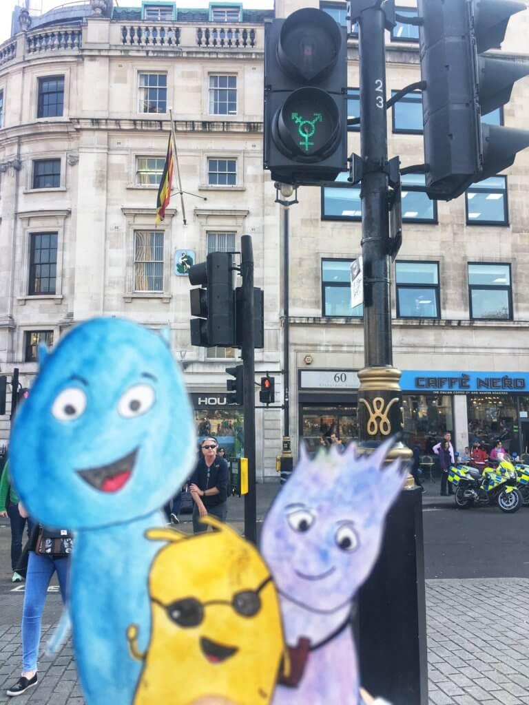 Alex, Valentin*a und Curly vor einer queere Ampel am Trafalgar Square London.